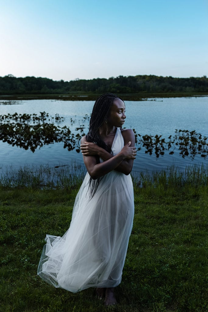 Wedding Photographer, A woman in a white dress stands before a quiet lake
