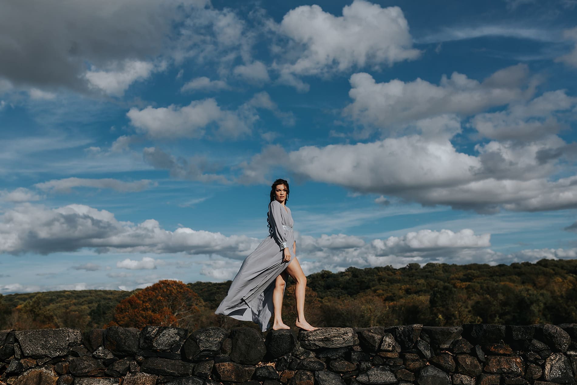 Wedding Photographer, Lady in flowing dress stands outdoors confidently on a cloudy day