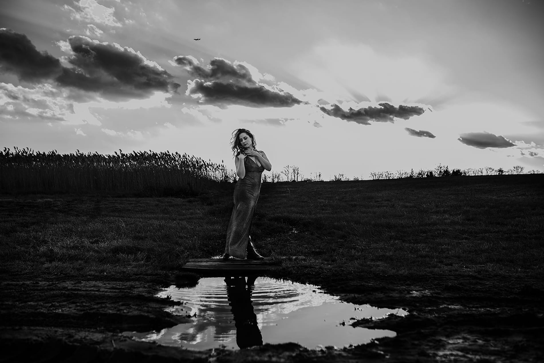 Wedding Photographer, Woman in a dress stands near water puddles in an open field