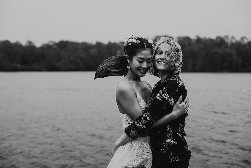 Family Photographer, Twoi women hold each other close smiling near a lake, the wind blowing their hair