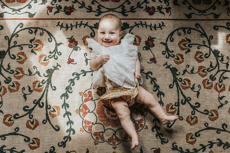 Family Photographer, A baby lays smiling on a patterned rug