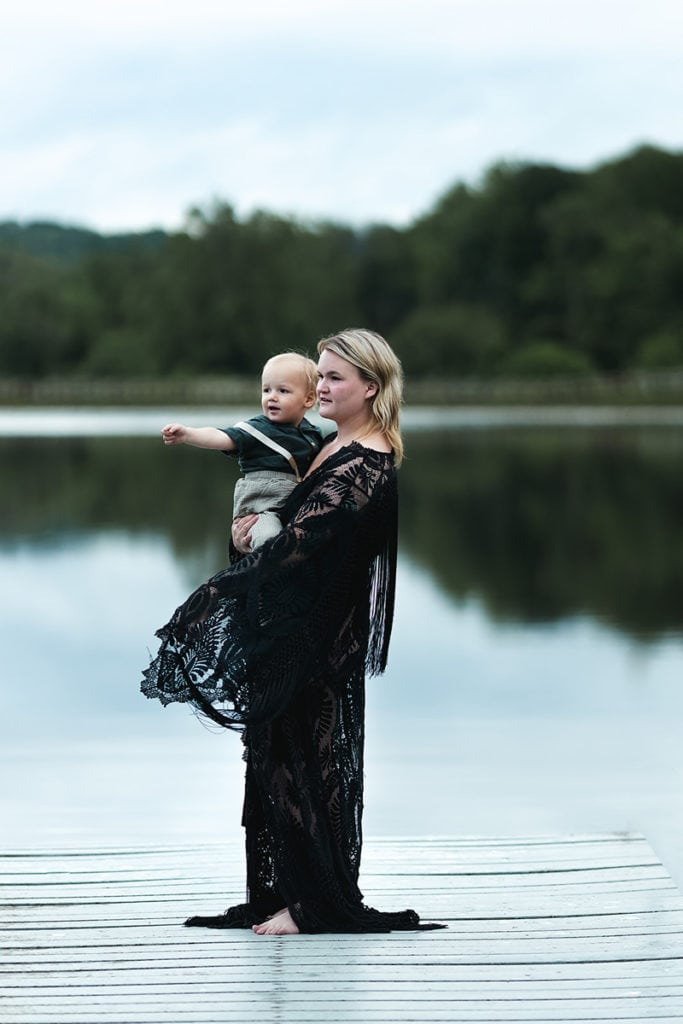 Family Photographer, Woman holds yound toddler son near lakeside